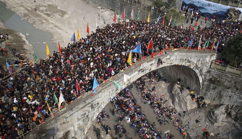 Эти люди считают, что если во время ежегодного трёхдневного фестиваля попасть на мост, то можно избежать многих неприятностей. Г. о. Мяньян, пр. Сычуань.