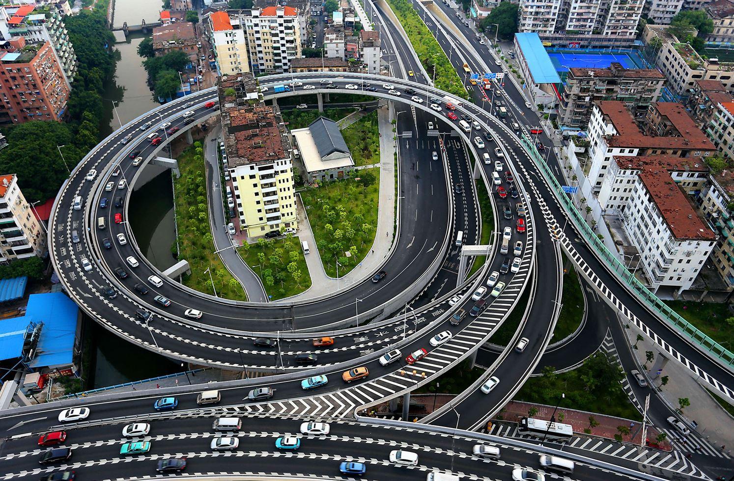 Два дома, окружённые автострадой в провинции Гуандун. Их хотели снести, но некоторые жители отказались покидать дома, поэтому автостраду достроили вокруг них.